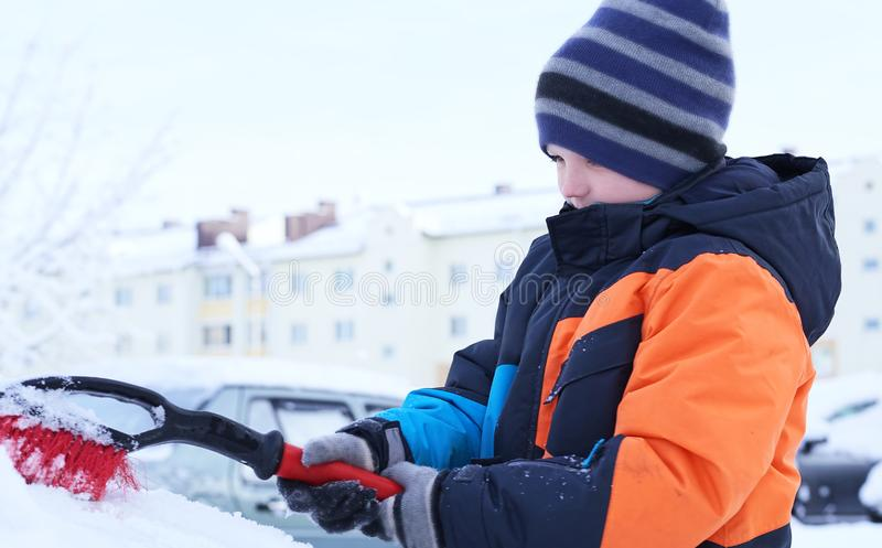 The boy standing near the car and holding a brush. The child cleans the car from snow. Teen Caucasian boy standing near the car and holding a brush. The child royalty free stock photo