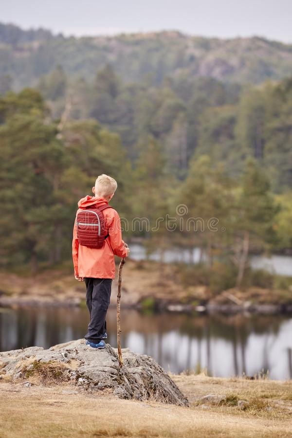 A boy standing on a rock admiring a view of lake, back view, Lake District, UK stock image