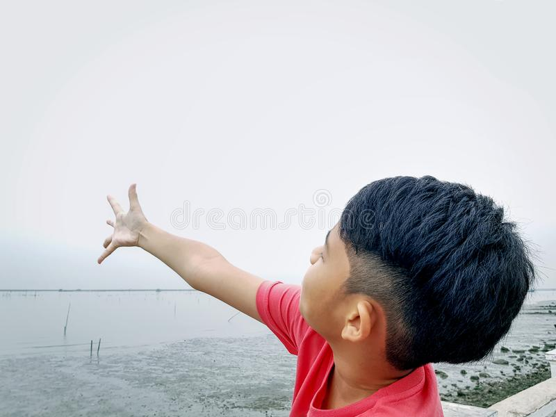 Boy Standing by the Sea Spreading Arm Up to Sky royalty free stock image