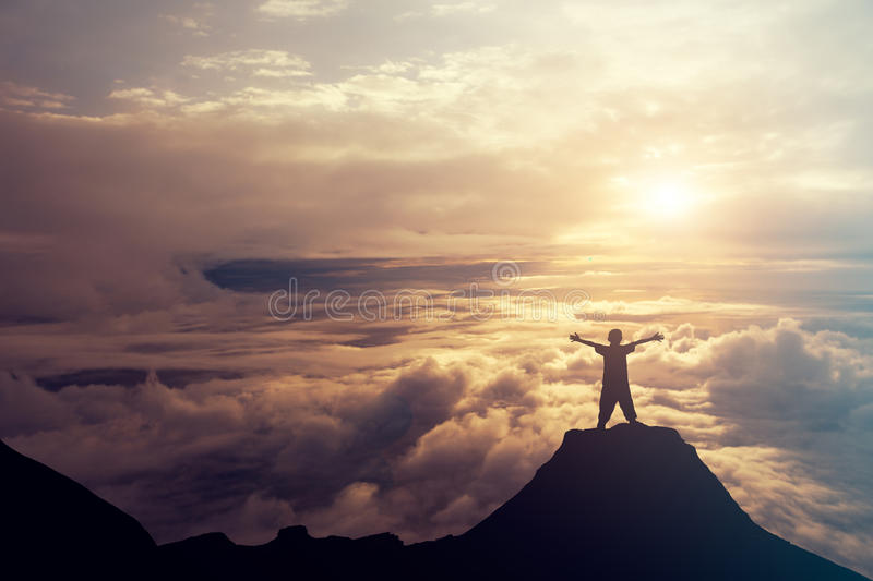A boy standing on the top of the mountain above the clouds. Success Concept. stock photography