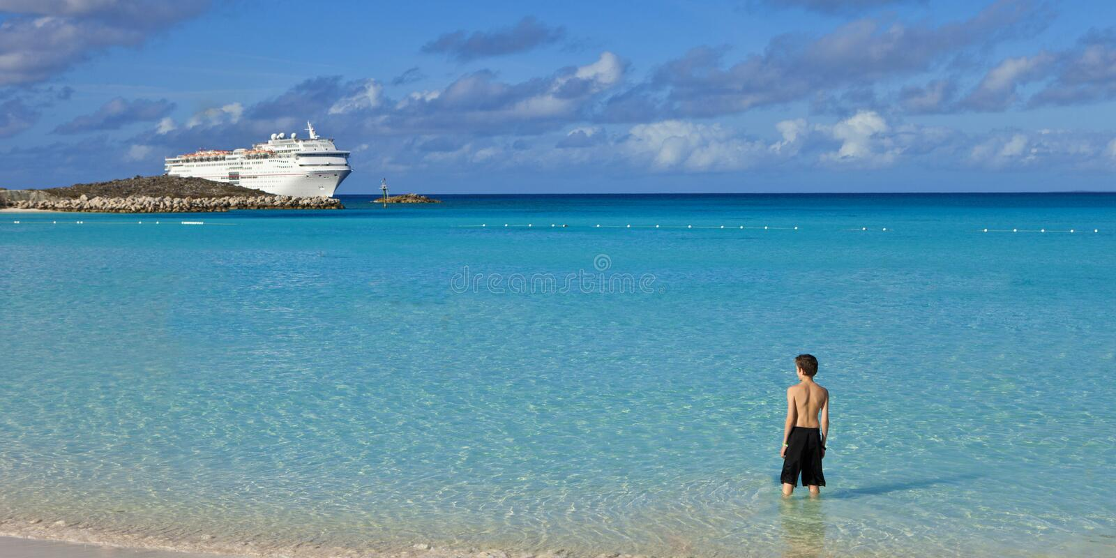 Download Boy Standing On Tropical Beach With Cruise Ship Stock Photo - Image: 28191158