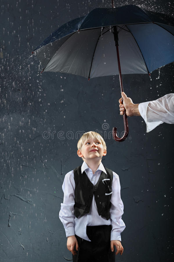 Boy standing under umbrella in rain royalty free stock photos