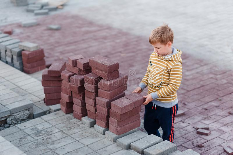 The boy stands near the building bricks. gray and red bricks . Children and professions. Children and construction royalty free stock images
