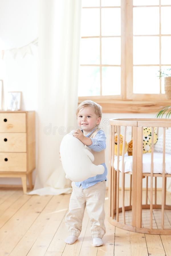 The boy stands next to the cot in the nursery and holds a toy in his hands. the kid is in kindergarten and plays. Eco-friendly chi stock image
