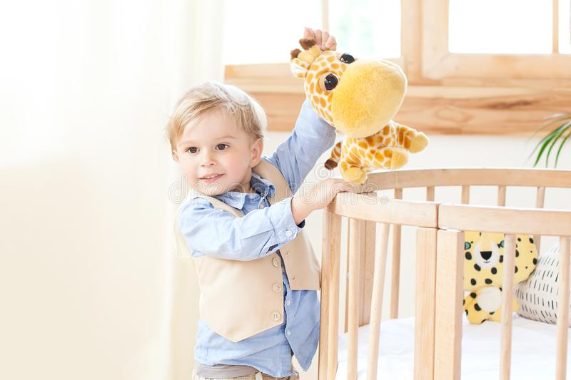 The boy stands next to the cot in the nursery and holds a toy in his hands. the kid is in kindergarten and plays. Eco-friendly chi stock photography