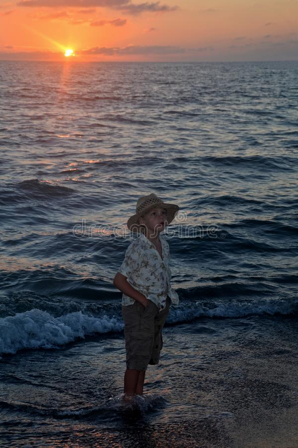 Boy stands in the water on the beach at the sundown and looks forwards. Small boy stands in the water on the beach at the sundown and looks forwards stock images
