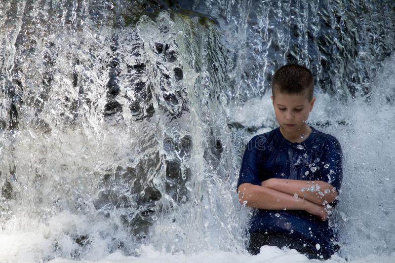 Boy stands in a waterfall stock image