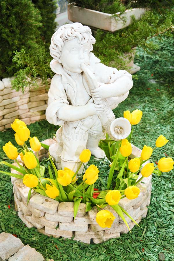 Boy statue with tulips stock photography