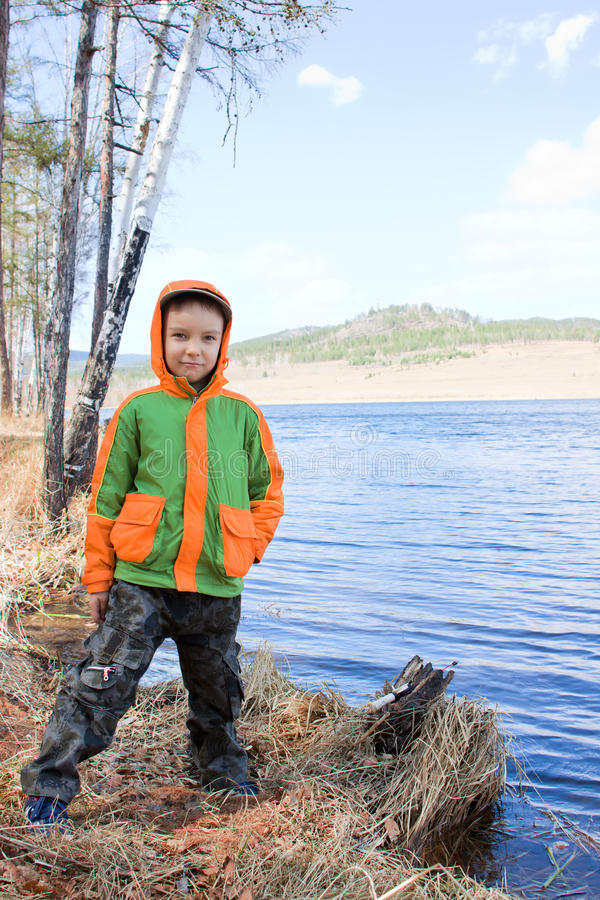 Boy staying near pond royalty free stock image