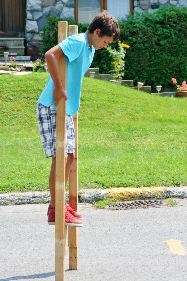 Download Boy on Stilts stock photo. Image of travel, teen, wooden - 33298300