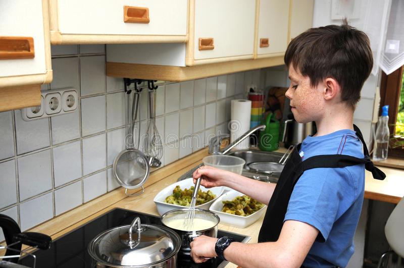 Boy stirring sauce. Hollandaise for a vegetable casserole royalty free stock photography