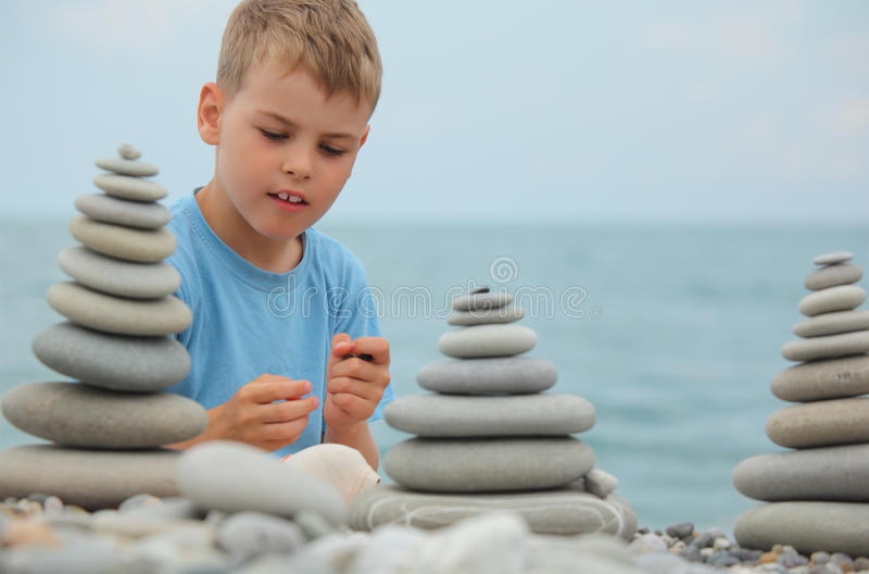 Boy And Stone Stacks On Pebble Beach Stock Images