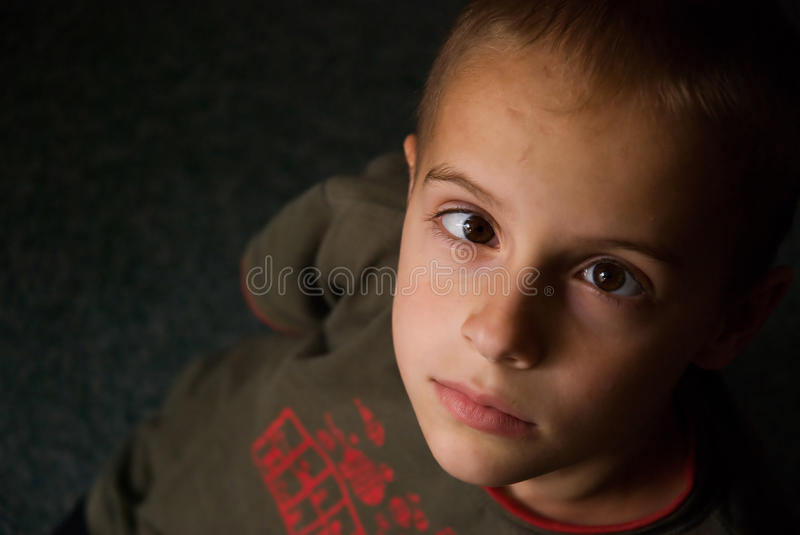 Boy with Strabismus. Portrait of a preteen boy with a strabismus, indoor on a dark green carpet using available light royalty free stock photography