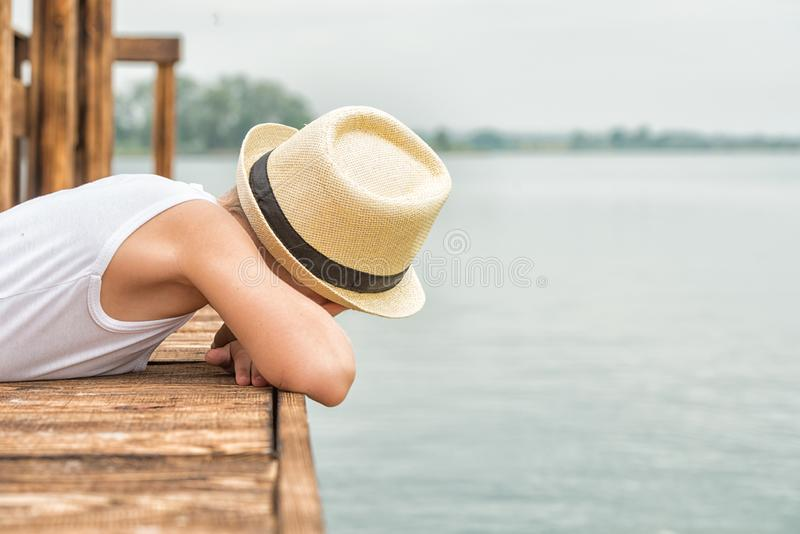 A boy in a straw hat lies on the wooden pier and looks at the water .Summer vacation on the lake. Summer vacation on the lakeA boy in a straw hat lies on the royalty free stock photos