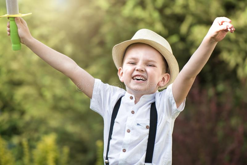 A boy in a straw hat walks and plays in the Park. royalty free stock photo