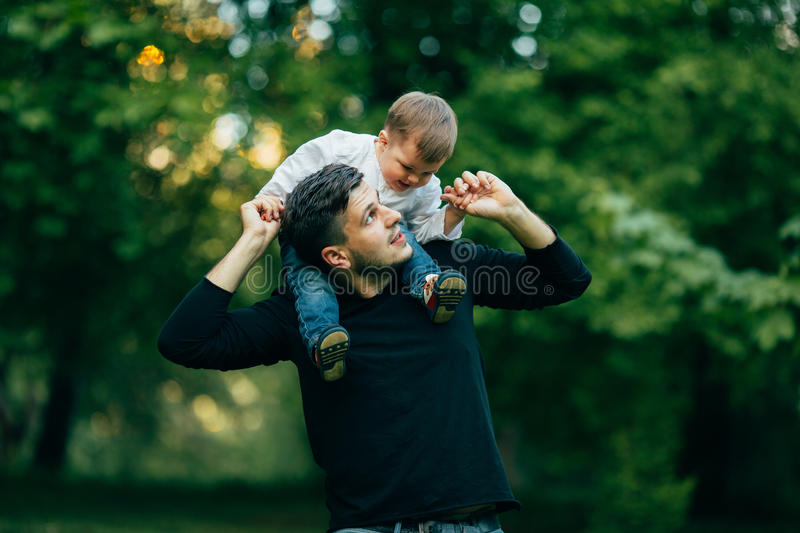 Boy stretching out hands while his father carrying him on shoulders stock photo
