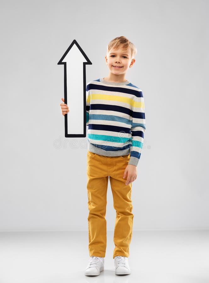 Boy in striped pullover with upwards thick arrow stock image