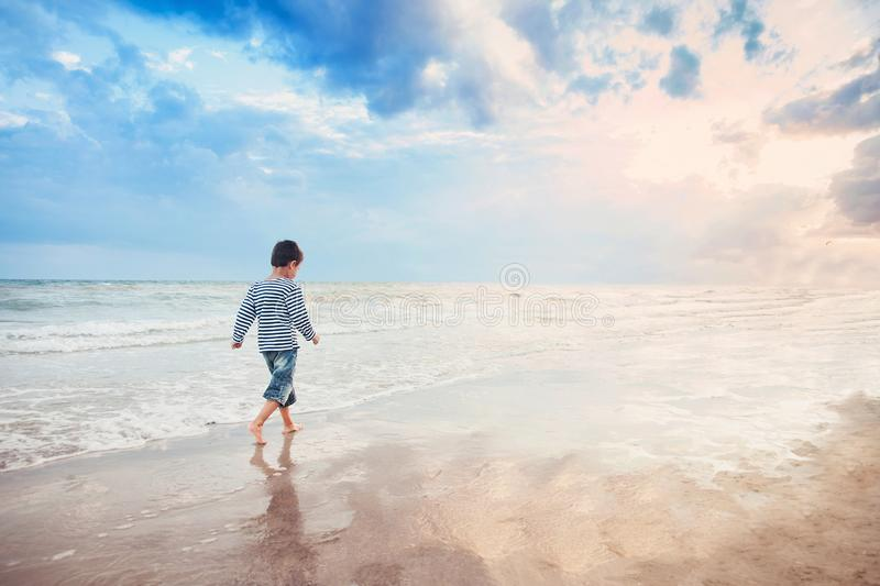 Child running on the beach. Summer vacation. happy kid playing on beach at the sunset time royalty free stock images