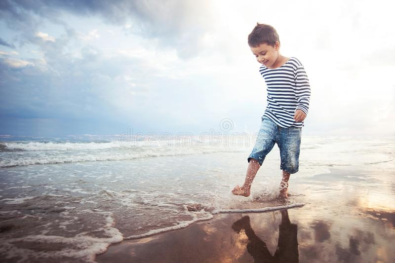 Child running on the beach. Summer vacation. happy kid playing on beach at the sunset time stock photography