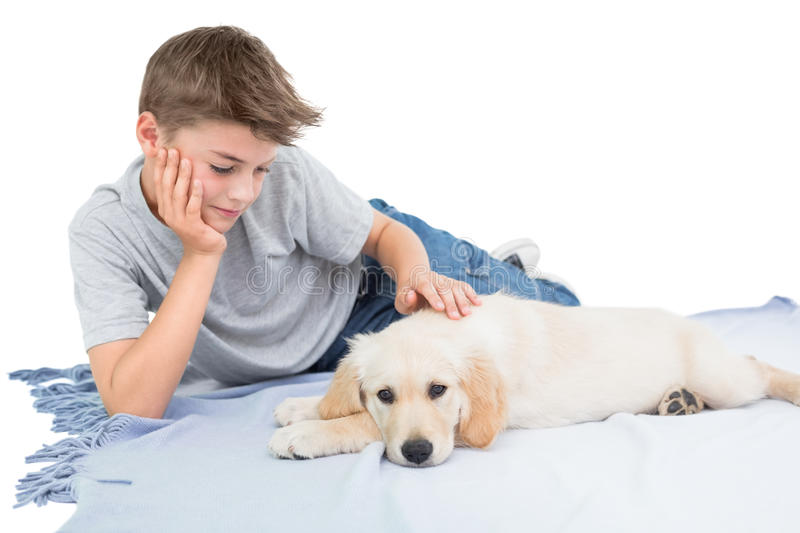 Boy stroking dog while lying on blanket. Over white background stock photo