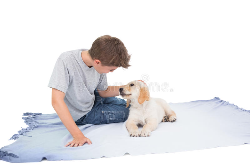 Boy stroking puppy on blanket stock image