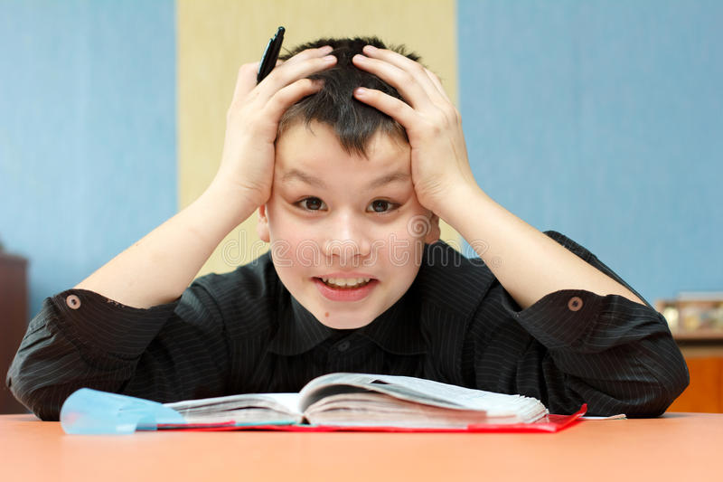 Boy student grabbed his head due to the difficult lessons royalty free stock image