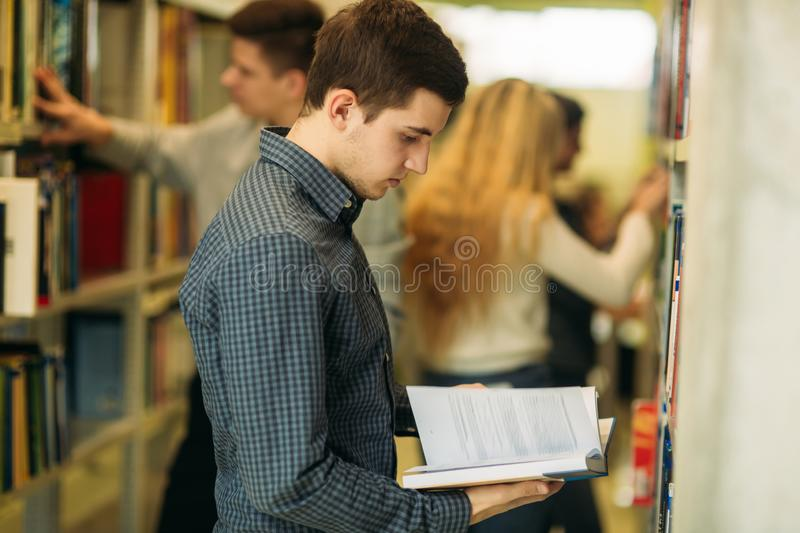 Boy student in library want to find some book. Student getting ready to exam. Boy student in library want to find some book stock photo