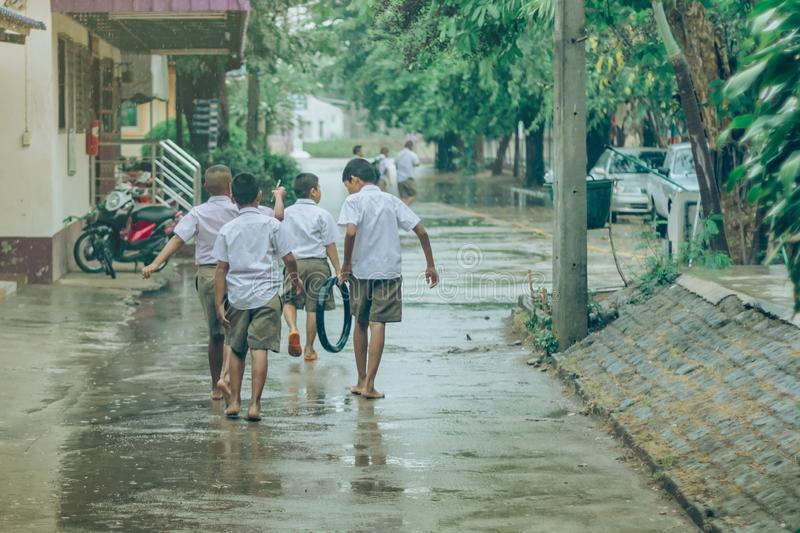 Boy students leave the classroom to walk on the street after heavy rain. In the school at Ho Chi Minh City, Vietnam stock photography