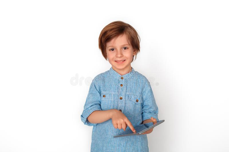 Boy studio standing isolated on grey browsing digital tablet looking camera joyful. Little boy studio standing isolated on grey wall browsing digital tablet ing royalty free stock image