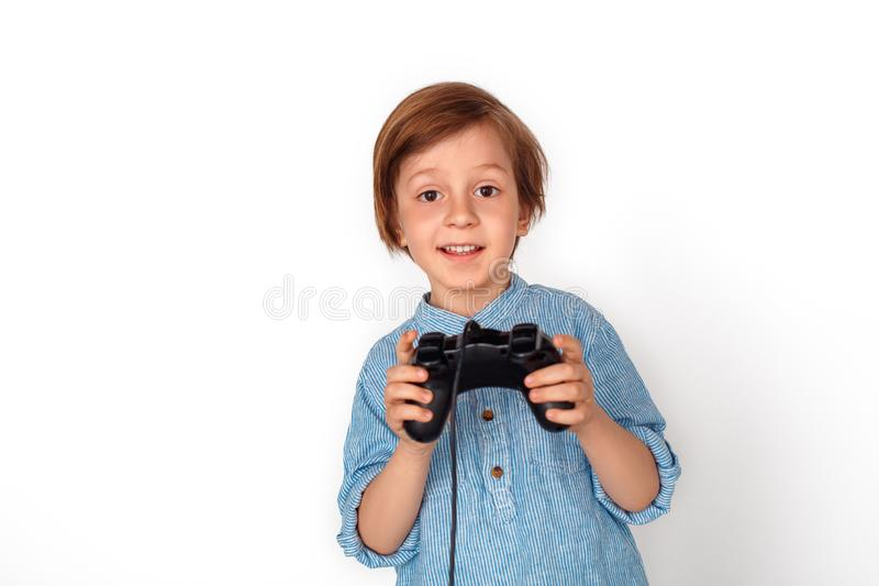 Boy studio standing isolated on grey with game controller playing game excited. Little boy studio standing isolated on grey wall holding controller playing game stock photography
