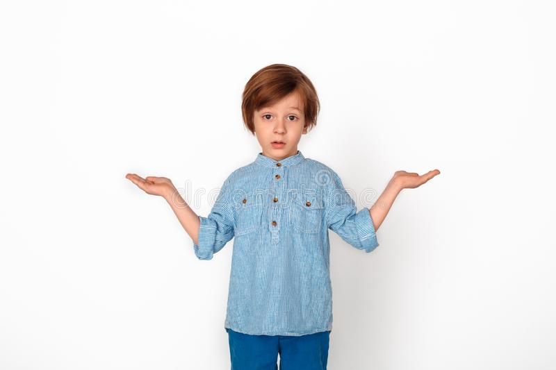 Boy studio standing isolated on grey hands aside looking camera confused. Little boy studio standing isolated on grey wall pointing aside with two hands looking royalty free stock photography