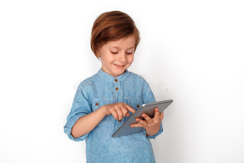 Boy studio standing isolated on grey playing game on digital tablet cheerful. Little boy studio standing isolated on grey wall playing game online on digital stock images