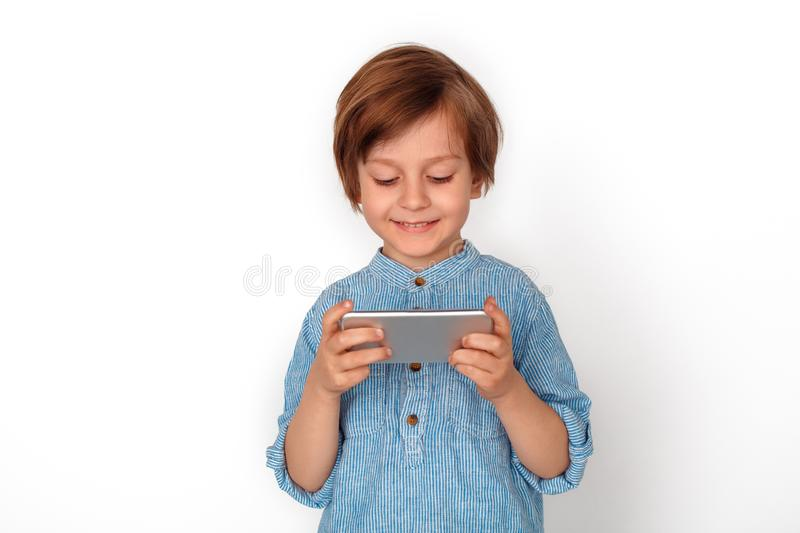 Boy studio standing isolated on grey playing game on smartphone happy. Little boy studio standing isolated on grey wall playing game online on smartphone smiling royalty free stock photography