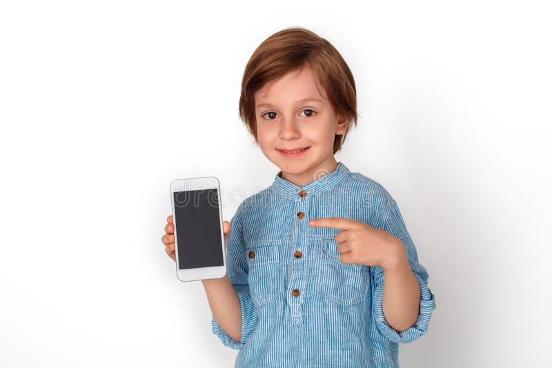 Boy studio standing isolated on grey pointing at smartphone screen looking camera friendly. Little boy studio standing isolated on grey wall pointing at royalty free stock photography
