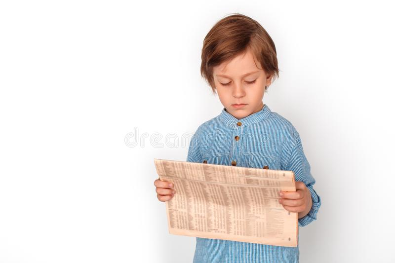 Boy studio standing isolated on grey reading newspaper concentrated. Little boy studio standing isolated on grey wall holding newspaper reading news concentrated stock photography