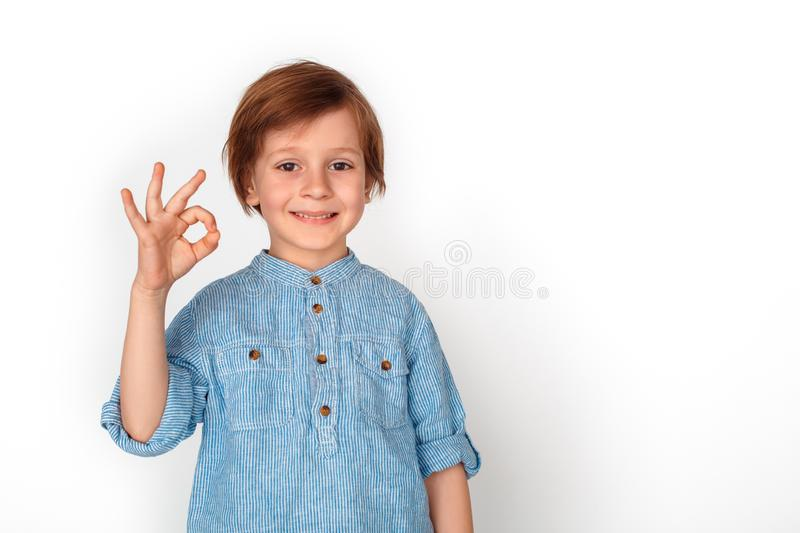Boy studio standing isolated on grey showing ok looking camera positive. Little boy studio standing isolated on grey wall showing ok sign looking camera smiling stock photo