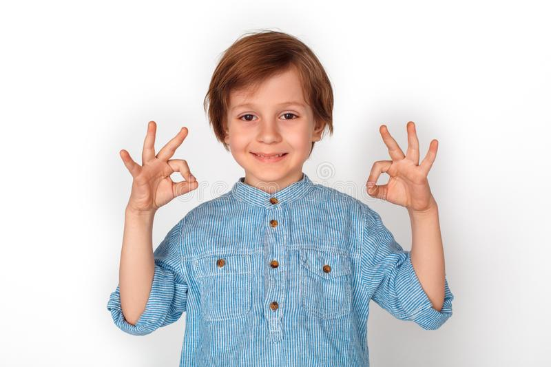 Boy studio standing isolated on grey showing ok sign with both hands looking camera playful. Little boy studio standing isolated on grey wall showing ok sign stock image