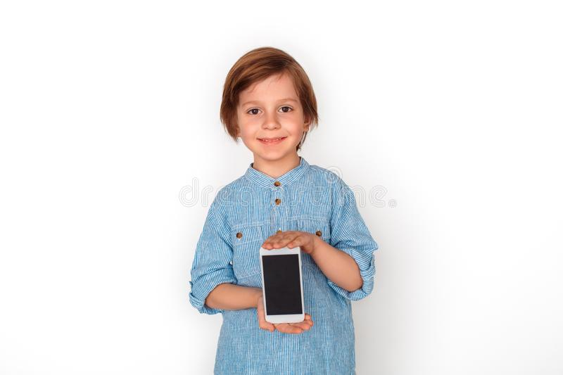 Boy studio standing isolated on grey showing screen of smartphone looking camera happy. Little boy studio standing isolated on grey wall showing smartphone stock photos