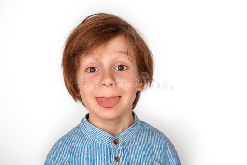 Boy studio standing isolated on grey showing tongue playful close-up. Little boy studio standing isolated on grey wall looking camera showing tongue playful face stock images
