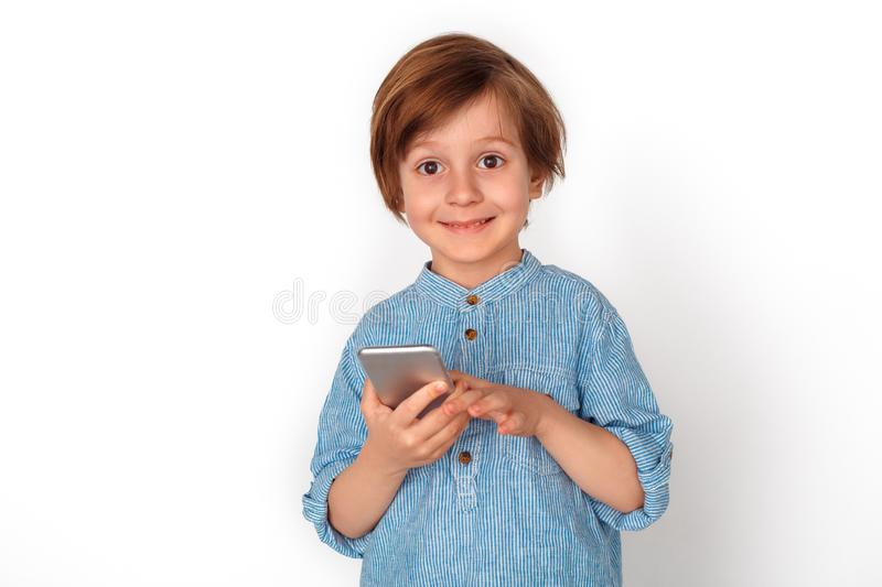 Boy studio standing isolated on grey with smartphone looking camera cheerful. Little boy studio standing isolated on grey wall holding smartphone looking camera royalty free stock photos