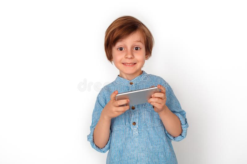 Boy studio standing isolated on grey watching video on smartphone looking camera cheerful. Little boy studio standing isolated on grey wall watching video online royalty free stock images
