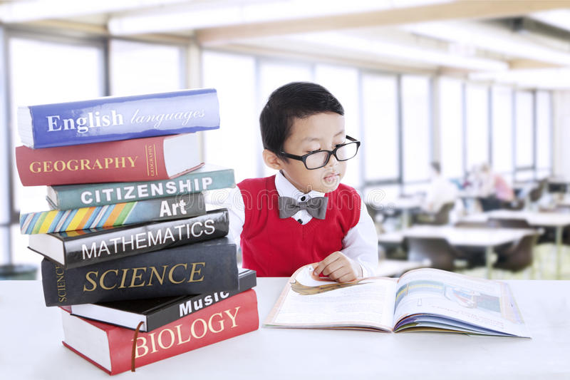Boy study literature books at library. Smart boy with glasses study different literature in the library stock photography
