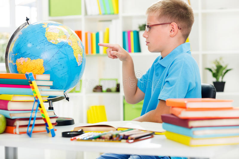 Boy studying geography with globe royalty free stock photos
