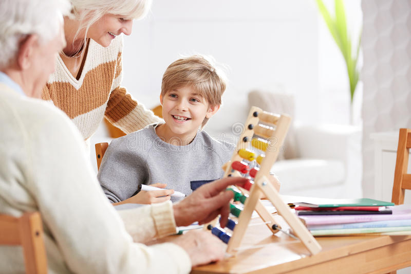 Boy studying math with grandparents stock photography