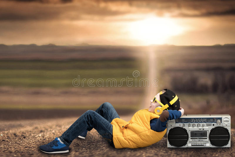Boy style hip-hop, listening to vintage tape recorder, lying on a country road. Boy style hip-hop, listening to vintage tape recorder stock images