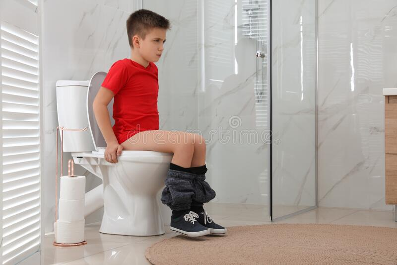 Boy sitting on the toilet stock photo. Image of beauty