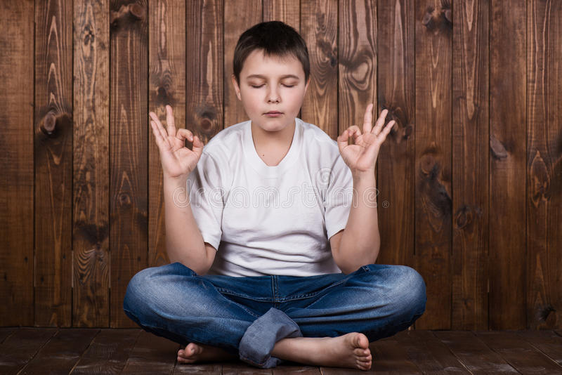 Boy in a suit in lotus position.  royalty free stock image