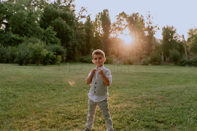 Boy in a suit, smiling, arranging his bowtie, looking at the camera in the park stock photos