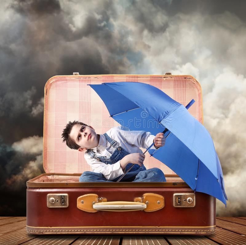 Boy with suitcase and umbrella royalty free stock photos