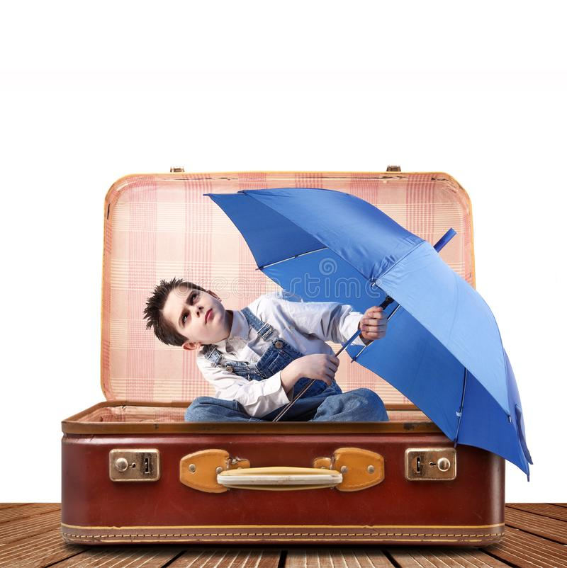 Boy with suitcase and umbrella stock images